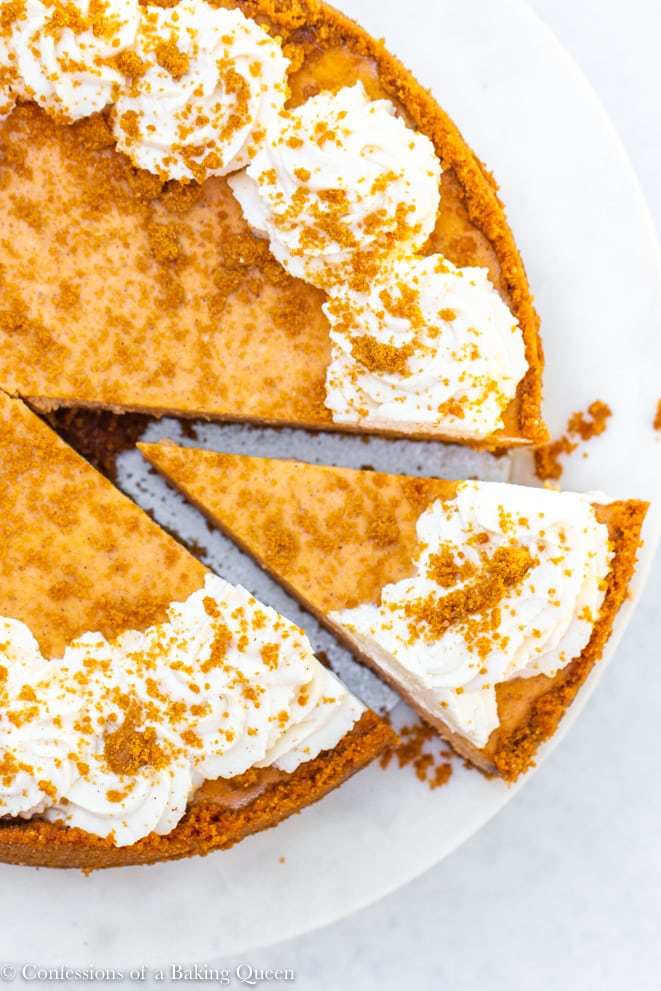 pumpkin cheesecake with a slice being taken out on a white marble cake stand on a white surface