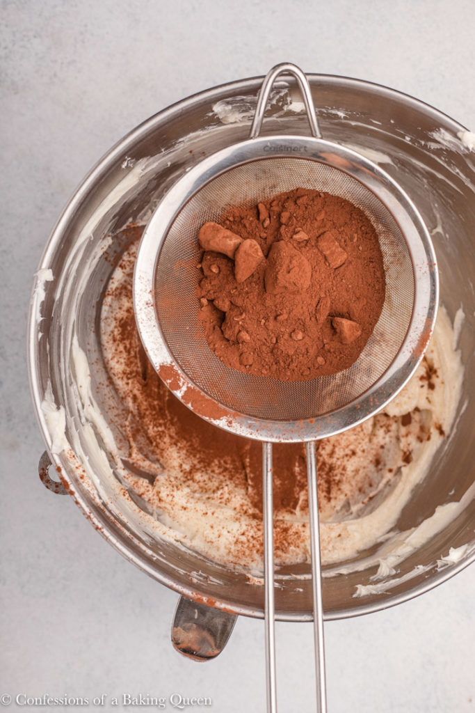 cocoa powder in a metal sieve over a bowl of cream cheese mixture on a light grey background