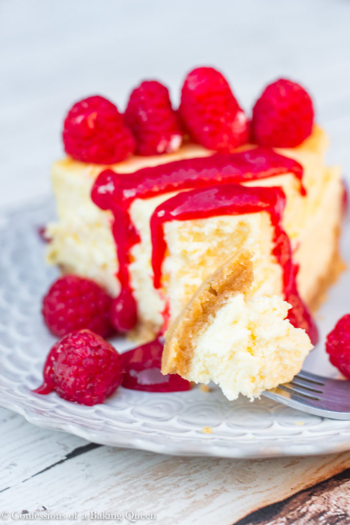 lemon cheesecake with red sauce and fresh raspberries on a purple plate