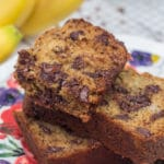 close up of baked slice of Chocolate Chip Banana Bread on a colorful plate with bananas and more banana bread in the background