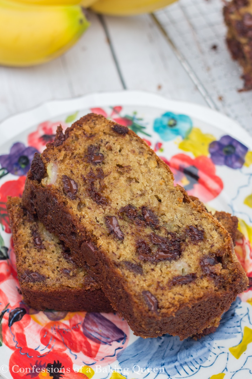 chocolate chip banana bread slices on top of another slice on a flowery colorful plate on a white wood background