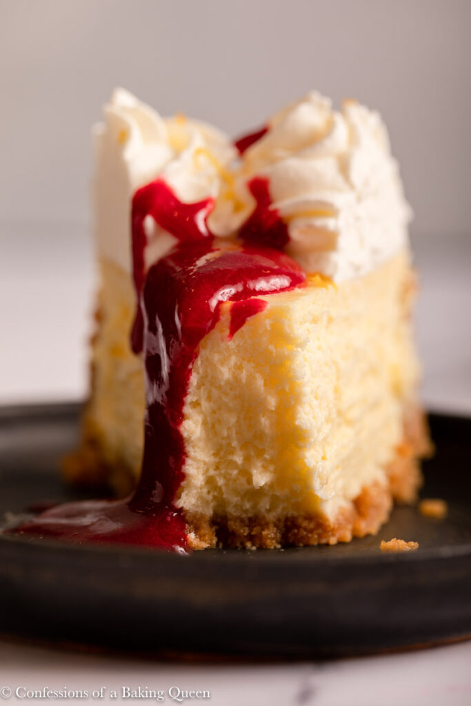 close up of lemon cheesecake with raspberry coulis dripping down on a black plate on a marble surface