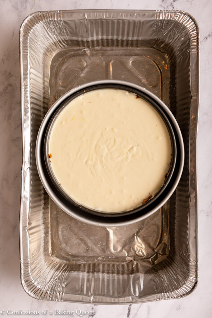 lemon cheesecake in a large roasting pan for a water bath on a marble surface