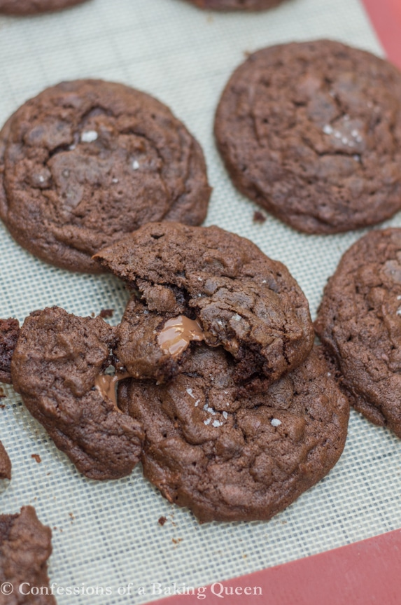 Sea Salt Double Chocolate Cookies broken open with oozing chocolate on a baking sheet