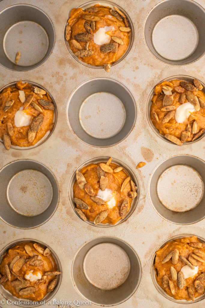 pumpkin cheesecake muffins topped with pumpkin seeds before baking