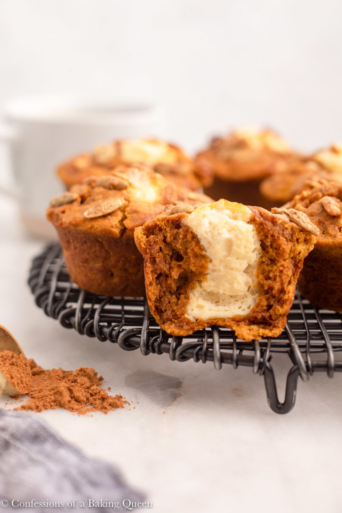 half of a pumpkin cheesecake muffin on a wire rack next to whole muffins