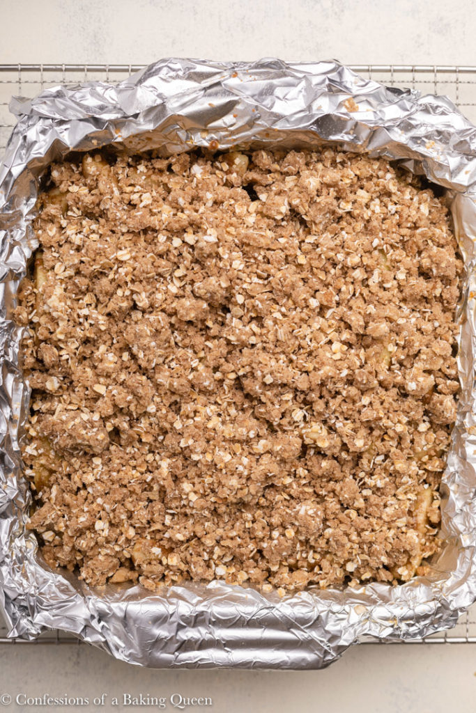 apple pie crumble bars in a foil lined baking pan on a wire rack