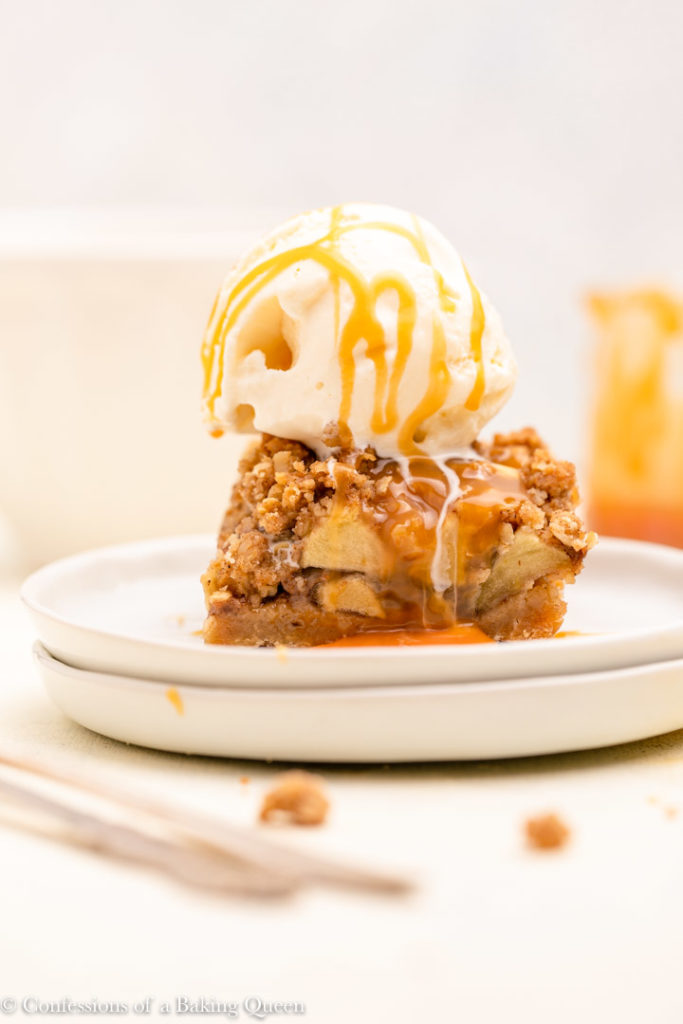 ice cream on top of a salted caramel apple pie bar on a white plate