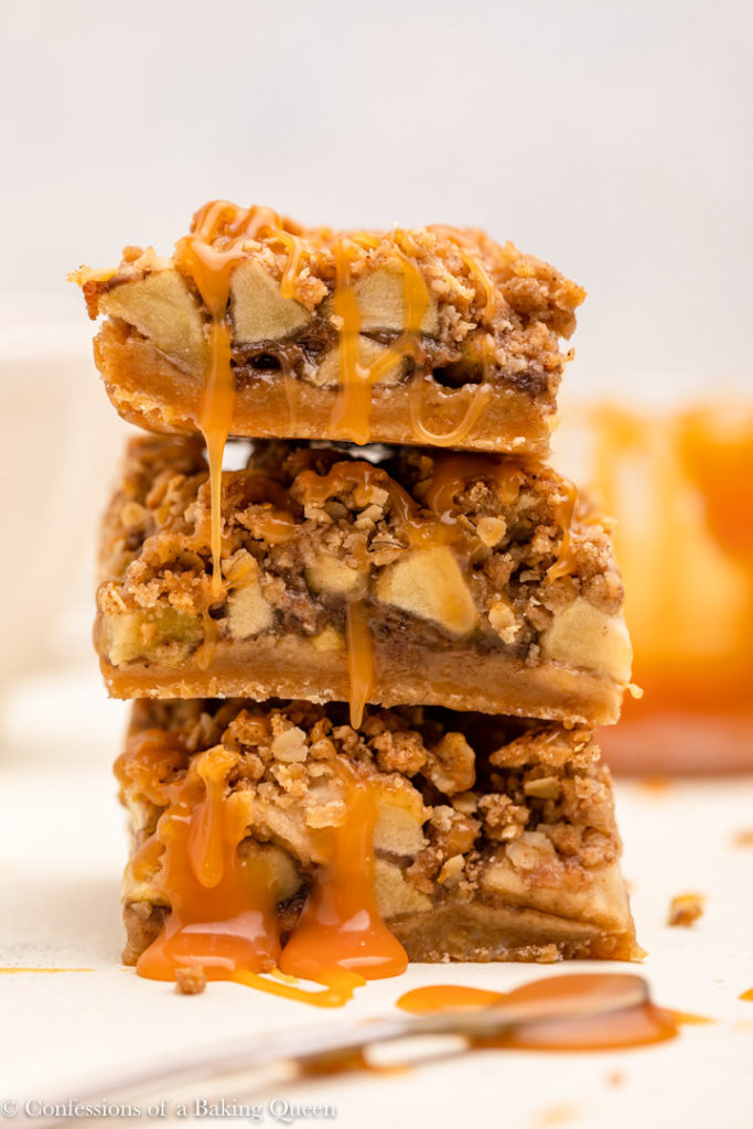three salted caramel apple pie bars on top of each other with caramel dripping down