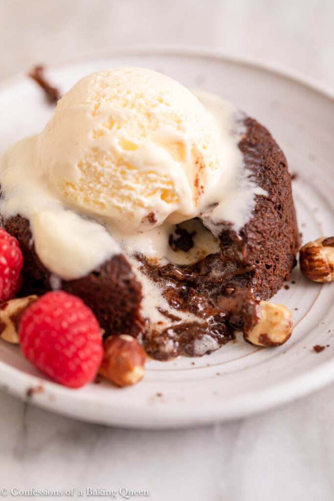 ice cream melting on top of nutella lava cake on a white plate on a white surface