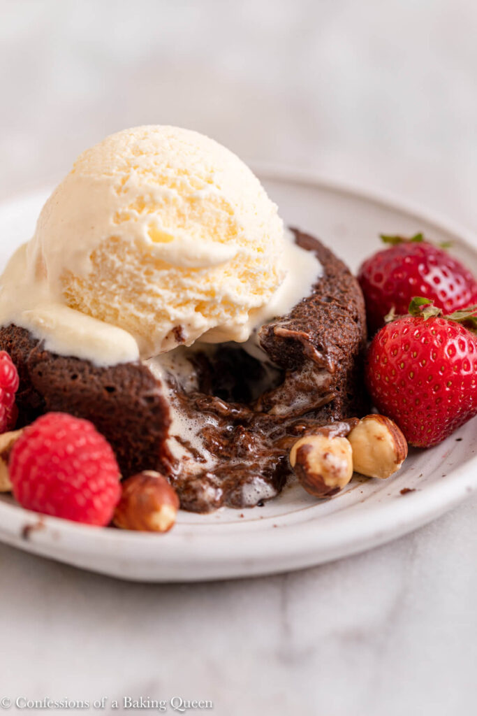ice cream melting on top of nutella lava cake with berries and hazelnuts on a white marble surface