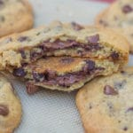Nutella Stuffed Chocolate Chip Cookie Recipe baked on a silpat lined baking sheet with one cookie broke in half