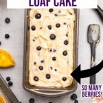 lemon blueberry loaf cake unabked in a loaf pan next to dirty spatula, a lemon squeezed and a liquid measuring cup