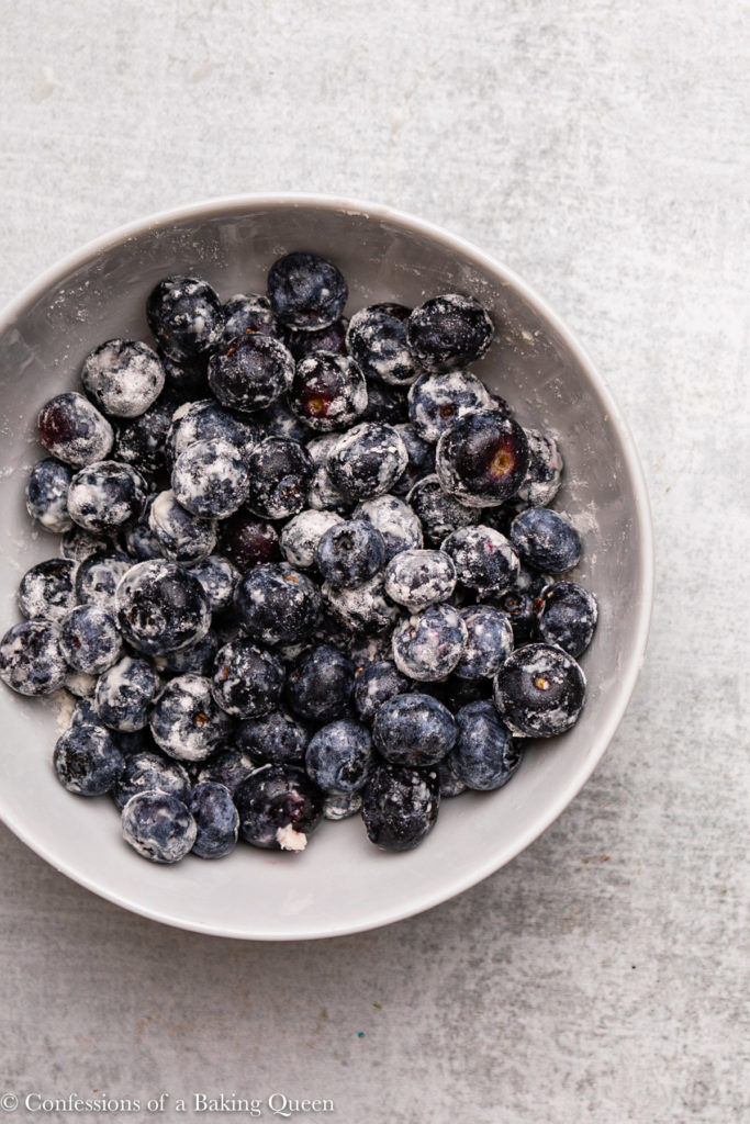 blueberries coated in flour in a small white bowl
