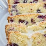 Blueberry Lemon Loaf Cake sliced on a white cake plate