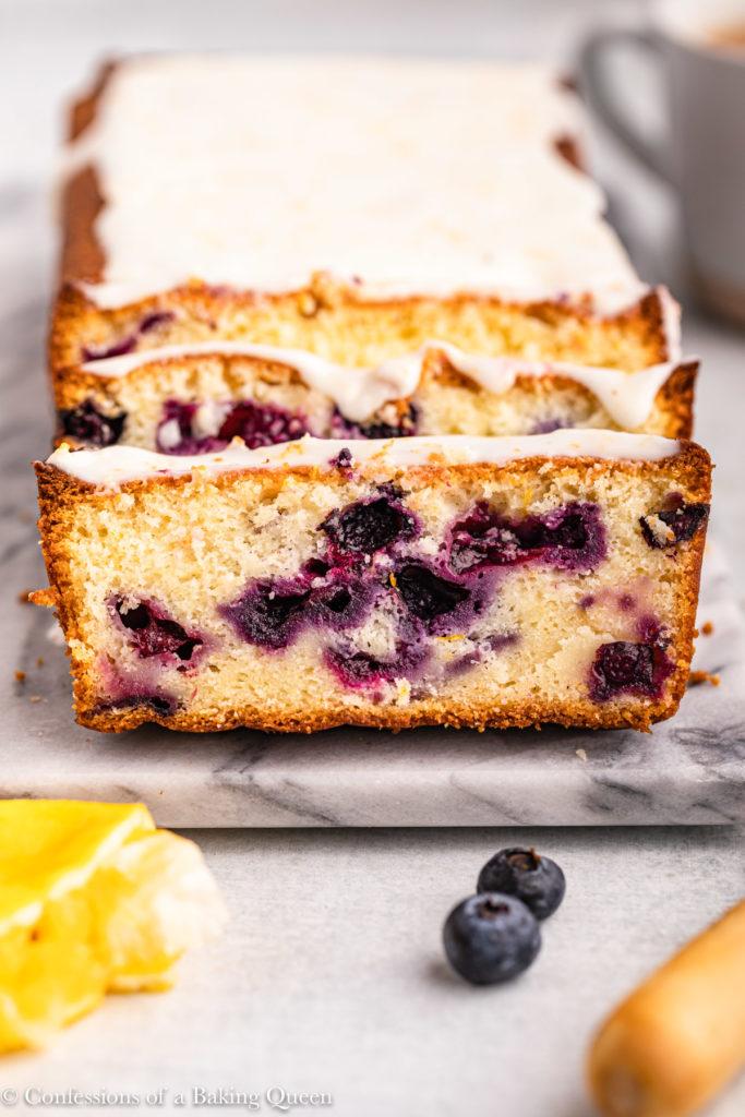 front on shot of lemon blueberry loaf cake sliced on a marble surface