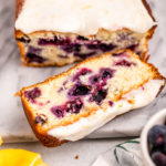 lemon blueberry loaf cake sliced on a marble surface