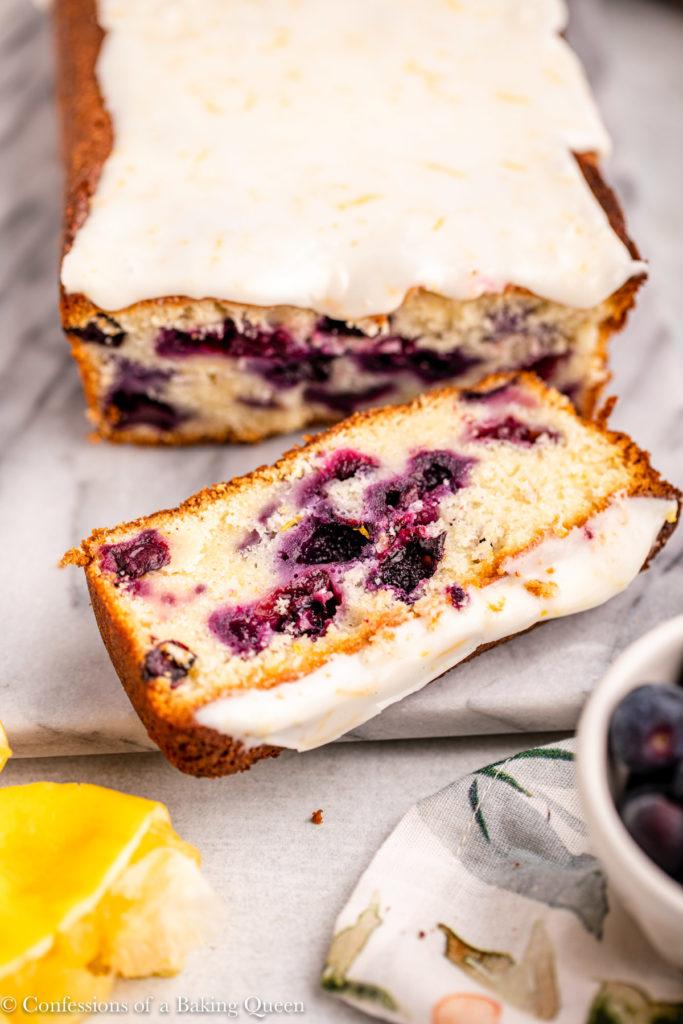lemon blueberry loaf cake sliced on a marble surface