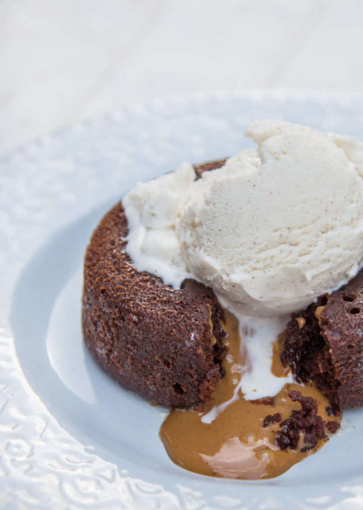 Cookie Butter Lava Cake baked on a blue plate cut open with cookie butter oozing out on a white background