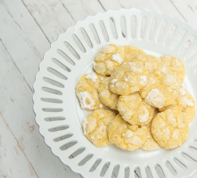 Chewy lemon cookies on a cake stand on a white background