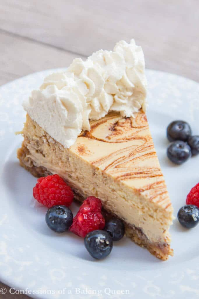 Cinnamon Roll Cheesecake with berries on a blue plate on a wood surface