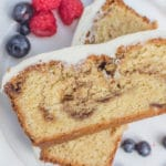 cinnamon roll pound cake stacked on top of each other on a white plate with fresh berries