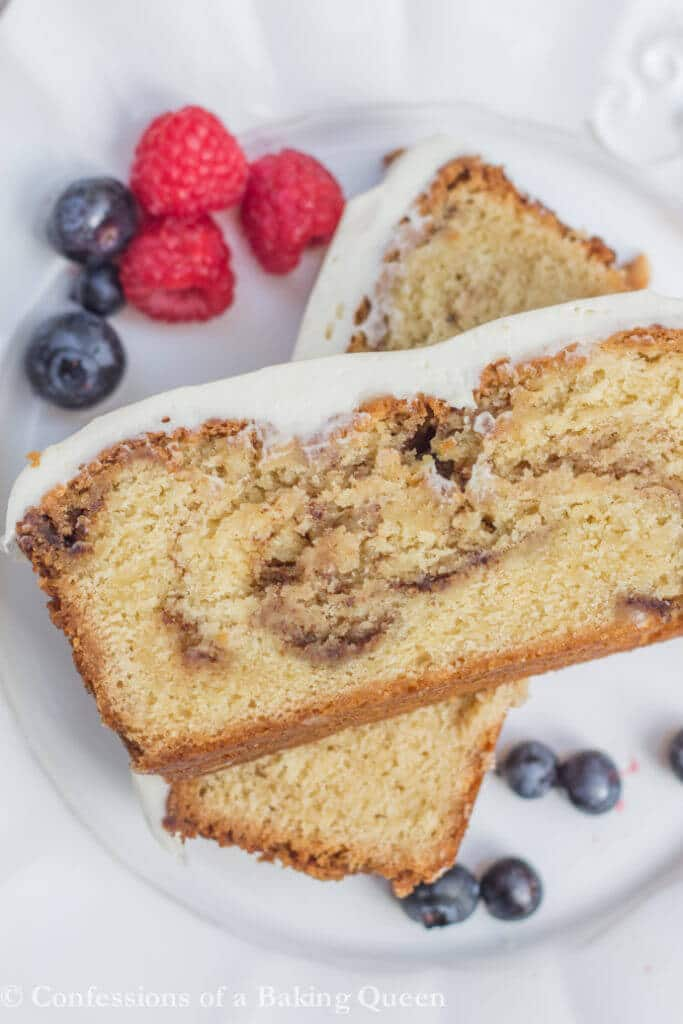 Cinnamon Roll Pound Cake stacked on top of each other on a white plate with berries on