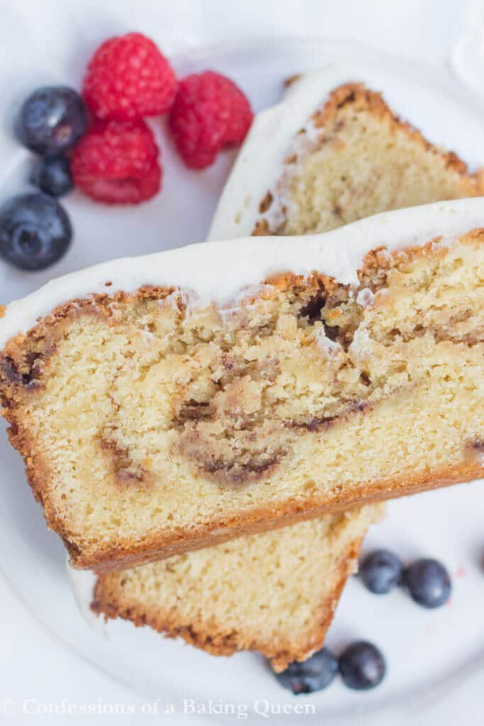 Cinnamon Roll Pound Cake stacked on top of each other on a white plate with berries on it