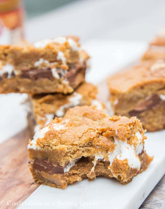 Cookie Butter S'mores Bars stacked in background with one bar with a bite taken out in the front on a marble surface