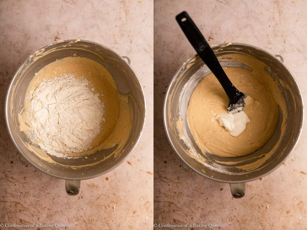 flour added to cake mixture then sour cream added in a metal mixing bowl on a light brown surface