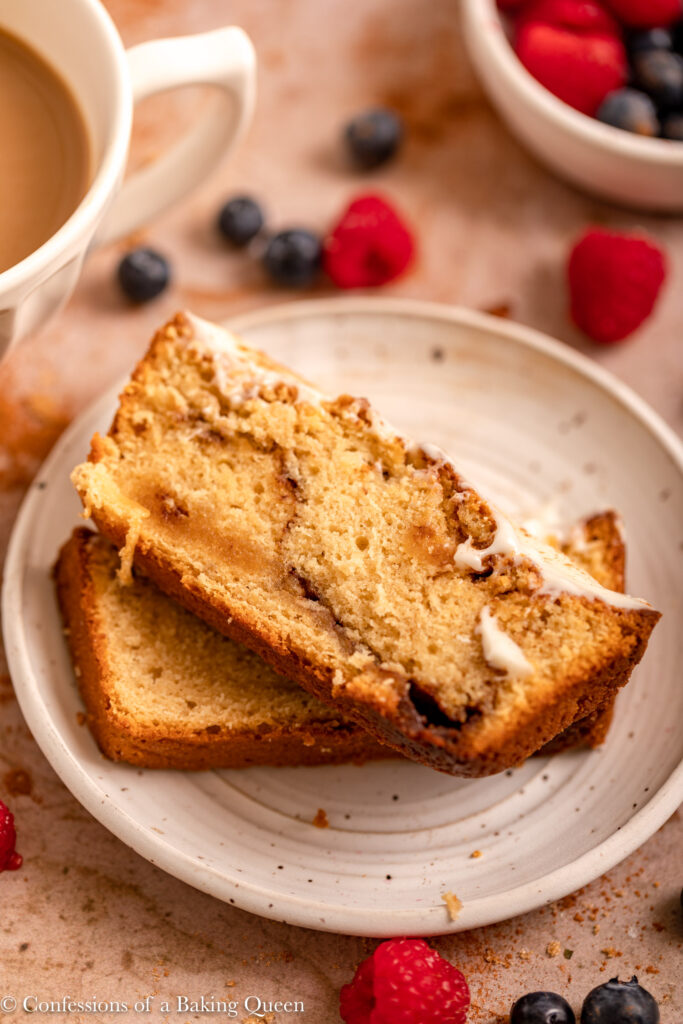 two slices of cinnamon roll pound cake on a white speckled plate next to a cup of coffee and berries on a light brown surface