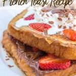 Nutella Strawberry French Toast up close on a white plate with a jar of nutella and a cup of coffee in the background