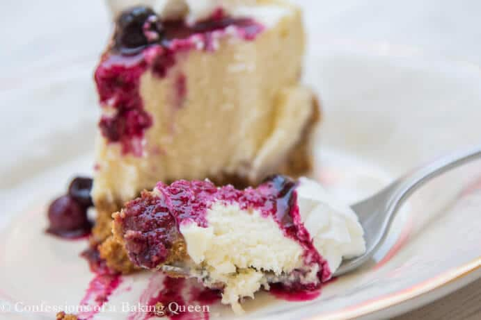 Blueberry Cheesecake bite on a fork on a cream plate