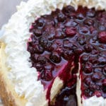 a close up of blueberry cheesecake missing a slice on a light grey surface