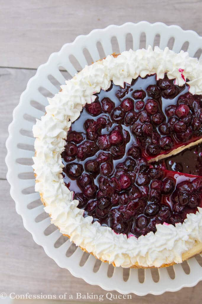 Blueberry Cheesecake overhead on a white cake plate on a wood background