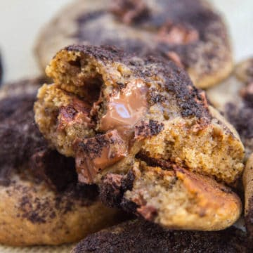 Espresso Chocolate Chunk Cookies with one cookie broken in half on a silpat lined baking sheet