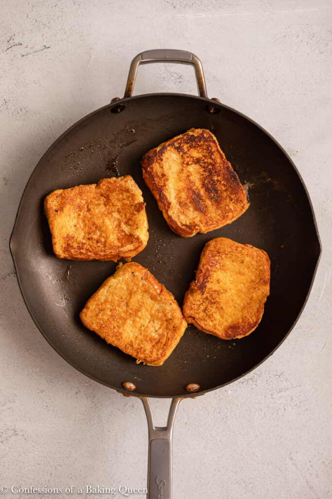 french toast cooking in a skillet o a light grey surface