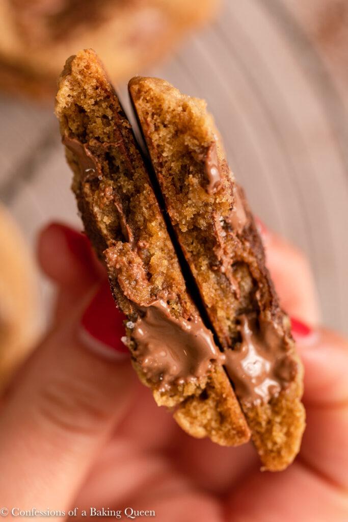 broken in half eaten espresso chocolate chip cookie over a rack of cooling cookies
