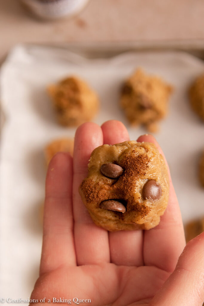hand holding a ball of cookie dough dipped in espresso powder over a tray of cookies
