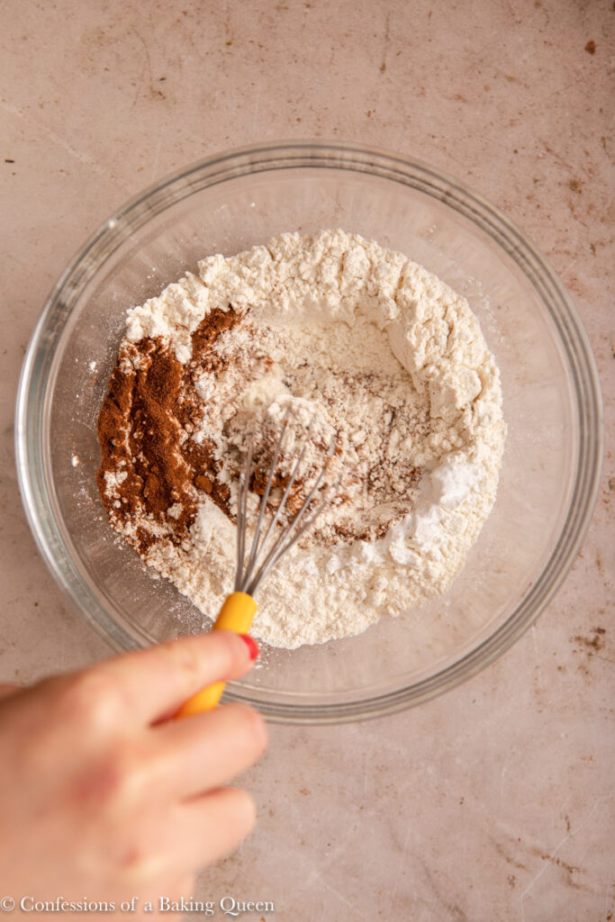 hand whisking dry ingredients together in a glass bowl on a light brown surface