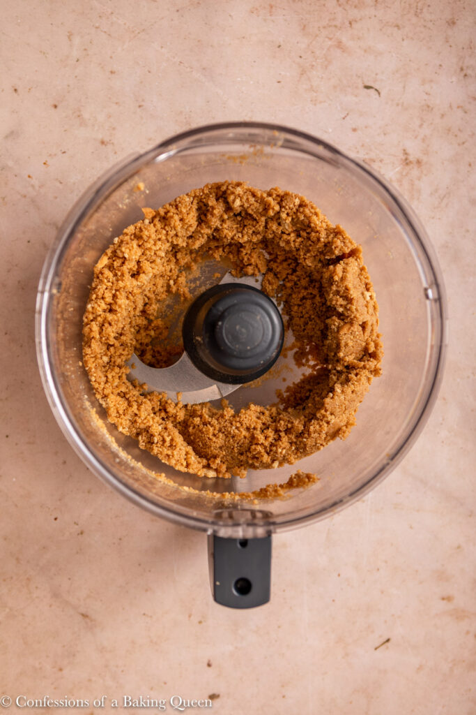 digestive biscuit and pecan cheesecake crust in a food processor on a light brown surface