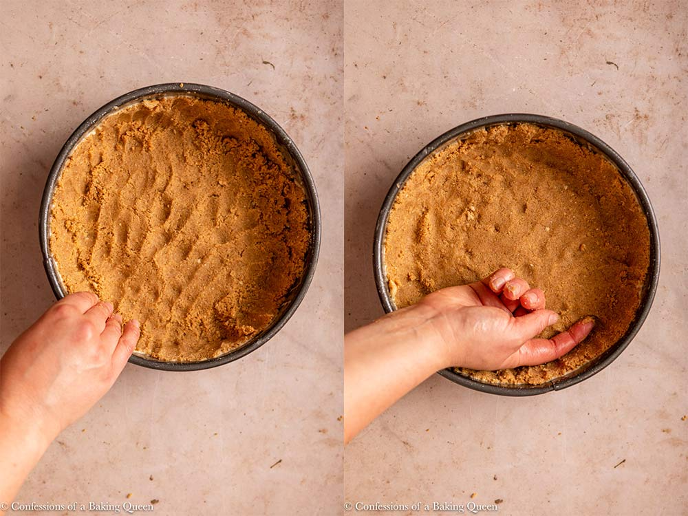 hand pressing crust crumbs into a springform pan on a light brown surface