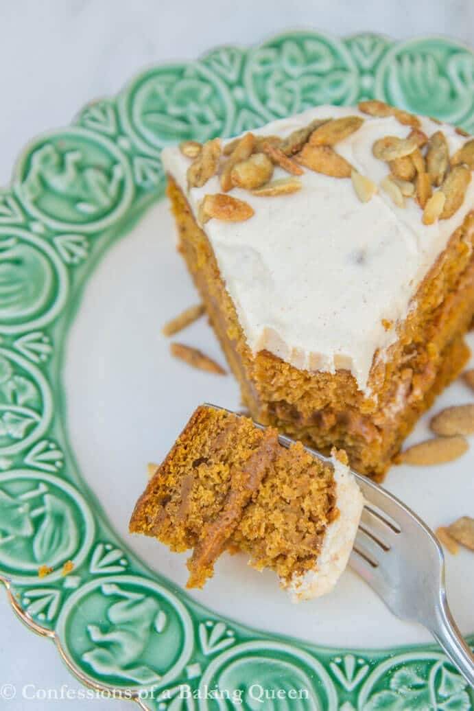 Brown Butter Pumpkin Cake on a white plate with green trim and a bite of the cake taken out