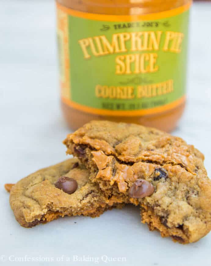 Pumpkin Chocolate Chip Cookie Butter cookies torn in half on white marble with a pumpkin spice cookie butter jar in background
