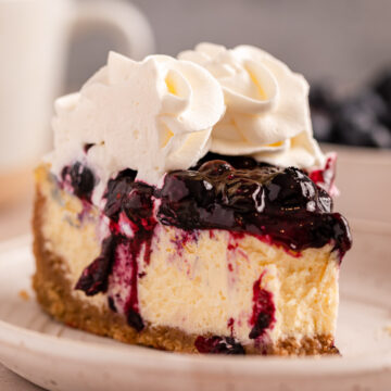 slice of half eaten blueberry cheesecake on a speckled white plate on a light brown surface