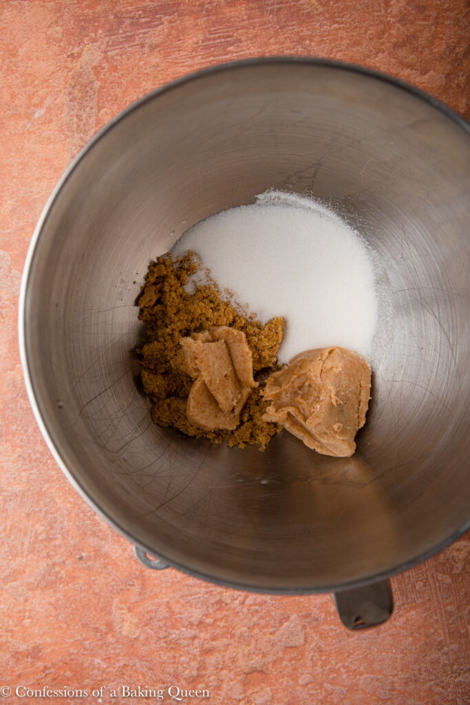 brown butter, sugar, and brown sugar in a metal mixing bowl on a reddish brown surface