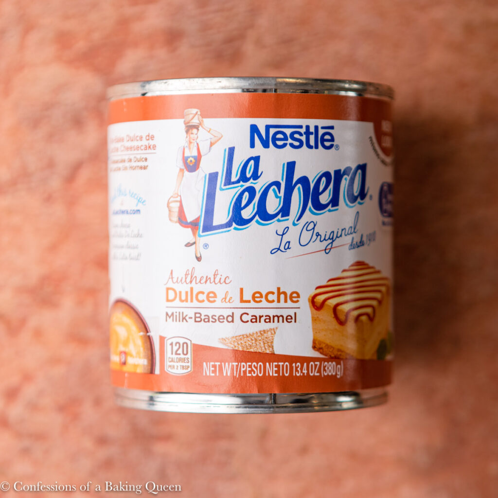 can of dulce de leche on a reddish brown background