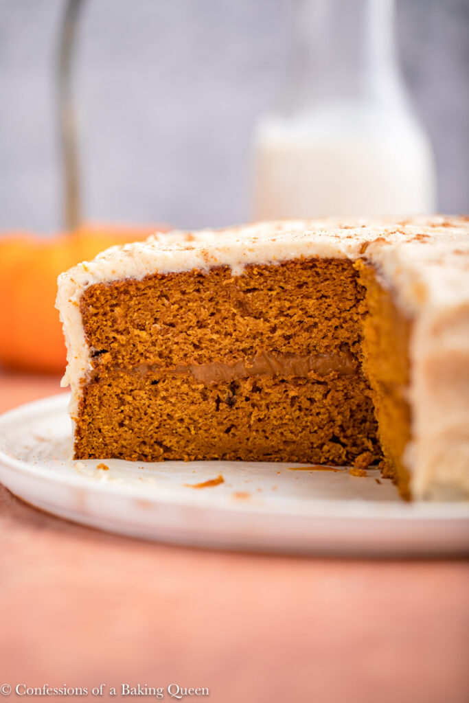 cut open showing the inside of a pumpkin layer cake on a white plate on a reddish brown background with a glass of milk and pumpkin in the background