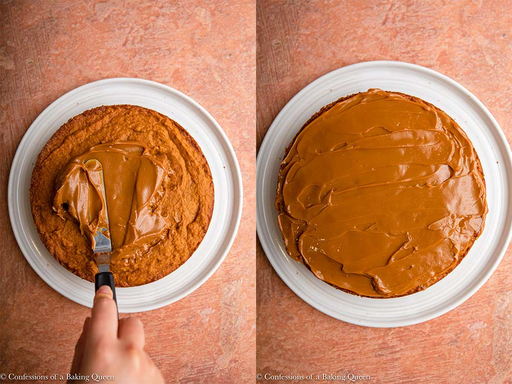 dulce de leche spread onto pumpkin cake layer on a white plate on a reddish brown surface