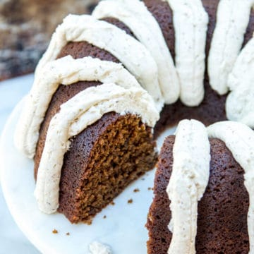 Guinness gingerbread cake with brown butter frosting served on a marble cake stand with a white and brown background